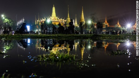 BANGKOK, THAILAND - OCTOBER 16:  Mourners are reflected in a puddle of rainwater as they pay their respects to Thailand's late King, outside the Grand Palace on October 16, 2016 in Bangkok, Thailand. Thailand's King Bhumibol Adulyadej, the world's longest-reigning monarch, died at the age of 88 in Bangkok's Siriraj Hospital on Thursday after his 70-year reign. The Crown Prince Maha Vajiralongkorn had asked for time to grieve the loss of his father before becoming the next king as nation waits for the coronation date.  (Photo by Leon Neal/Getty Images)