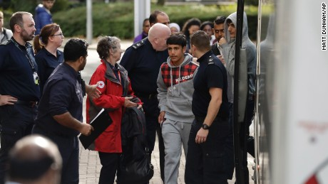 Two young migrants get off a bus at Lunar House in south London.