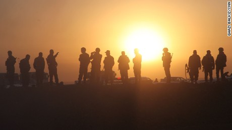 Kurdish Peshmerga infantry forces stand on a berm at Sunrise as they watch and take photos of Kurdish tanks and APCs crossing into ISIS held territory as mission to liberate Mosul from ISIS gets underway. (CREDIT: Ghazi Balkiz/CNN)