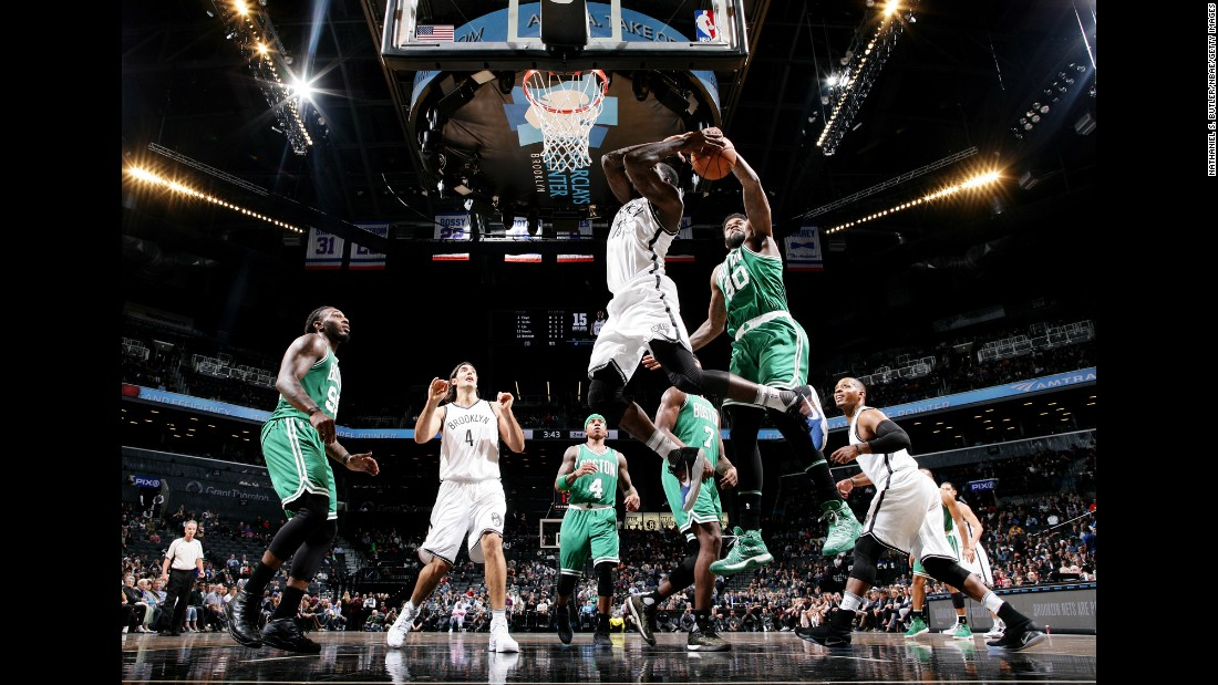 Boston's Amir Johnson blocks Brooklyn's Anthony Bennett during an NBA preseason game in New York on Thursday, October 13.