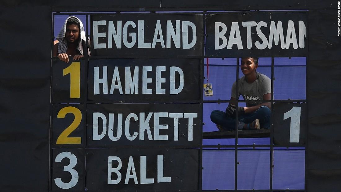 Scoreboard operators watch the English cricket team play the Bangladesh Cricket Board XI in Chittagong, Bangladesh, on Saturday, October 15.