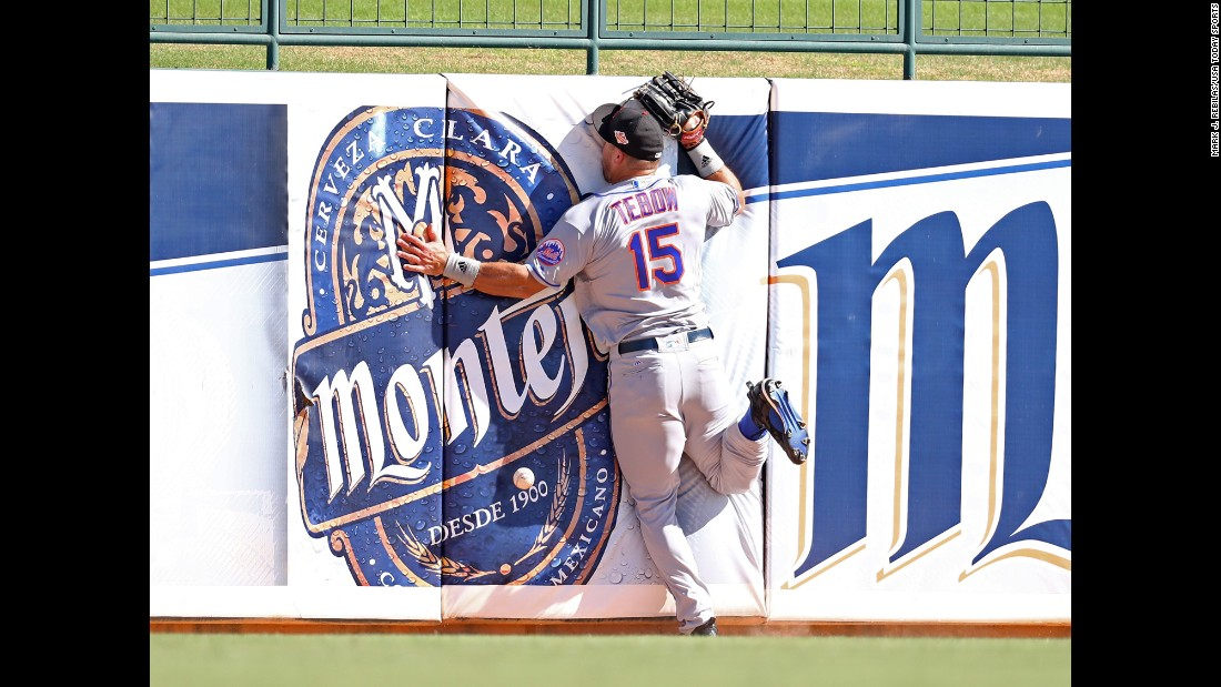 """Tim Tebow crashes into the outfield wall as he tries to catch a fly ball during a minor-league baseball game in Glendale, Arizona, on Tuesday, October 11. The former Heisman Trophy winner, who last played in the NFL in 2012, <a href=""""http://www.cnn.com/2015/05/08/opinions/coy-wire-tim-tebow-chases-dream/"""" target=""""_blank"""">is now giving pro baseball a shot.</a>"""