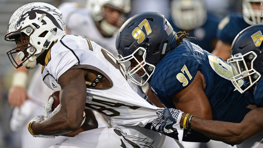 Western Michigan wide receiver Corey Davis is grabbed by Akron defenders during a college football game in Akron, Ohio, on Saturday, October 15.