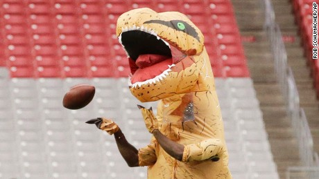 Arizona Cardinals cornerback Patrick Peterson catches a pass while dressed as a dinosour prior to an NFL football game against the New York Jets, Monday, Oct. 17, 2016 in Glendale, Ariz. (AP Photo/Rob Schumacher, Arizona Republic via AP)