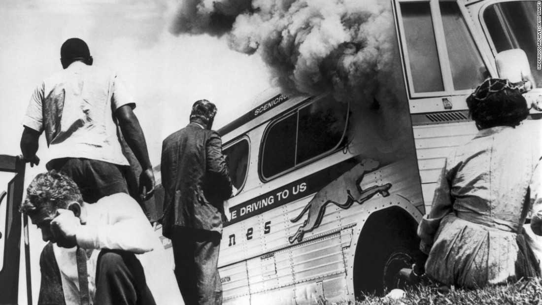 Freedom Riders sit on the ground after their bus was set ablaze by a mob of whites in Alabama in 1961. The Freedom Riders risked their lives to make America better but are not commonly seen as patriots.