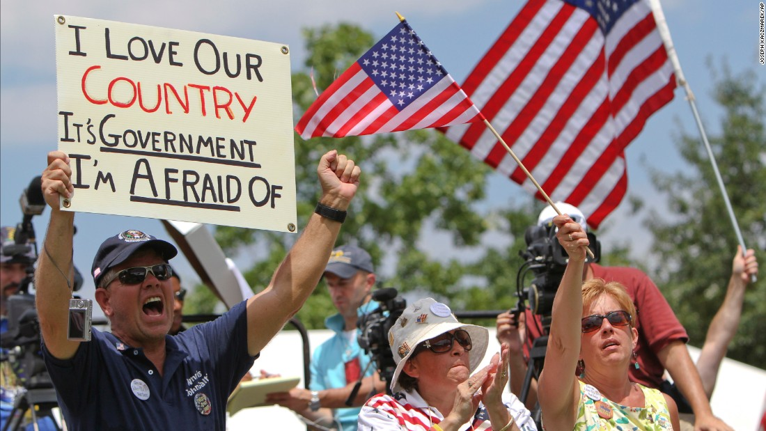 """People hold signs and wave flags during the """"Uni-Tea"""" tea party rally at Independence Mall in Philadelphia in July 2010. This is the """"love it or leave it"""" attitude that has defined traditional patriotism."""