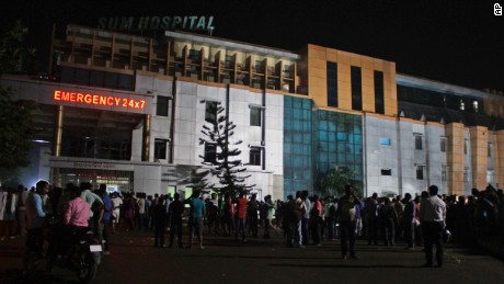 People gather outside the private Sum Hospital after a fire broke there on October 17, 2016.