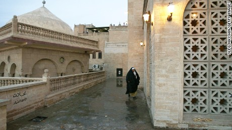 An Iraqi woman walks near the mosque of the Prophet Usuf October 24, 2002.