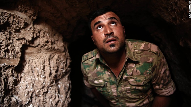 A Peshmerga fighter looks out of the entrance of an ISIS tunnel in Badana.