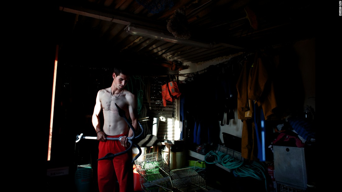 Fran, 26, checks the anchor of his small boat before heading out to sea. He is the youngest percebeiro in his family. He was forced to join the family business when Spain's real-estate market collapsed.