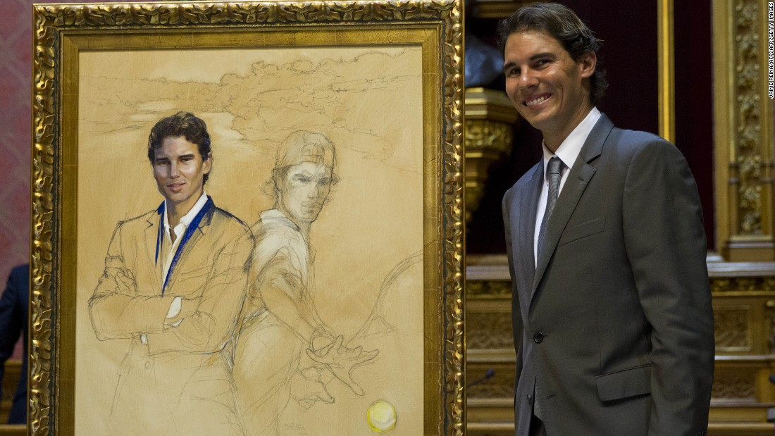 """Nadal poses next to a painting depicting himself during a ceremony in Palma where he received the title of """"Favorite Son of Mallorca"""" in December 2014."""