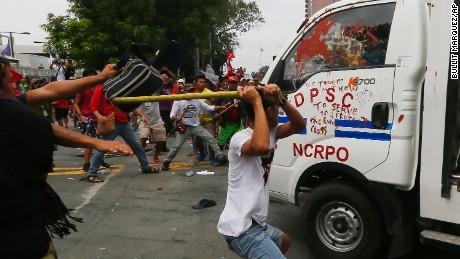 Protesters hit a Philippine National Police van after it rammed into protesters.