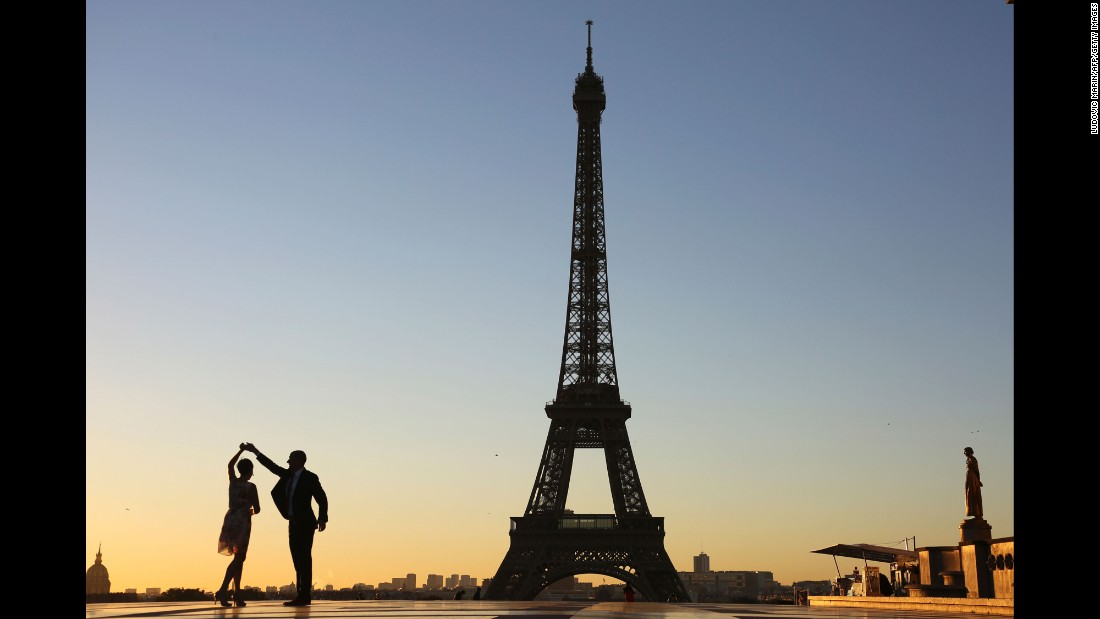 A couple dance at sunrise on Trocadero Plaza in front of the Eiffel tower. The tower celebrated its 127th anniversary in 2016.
