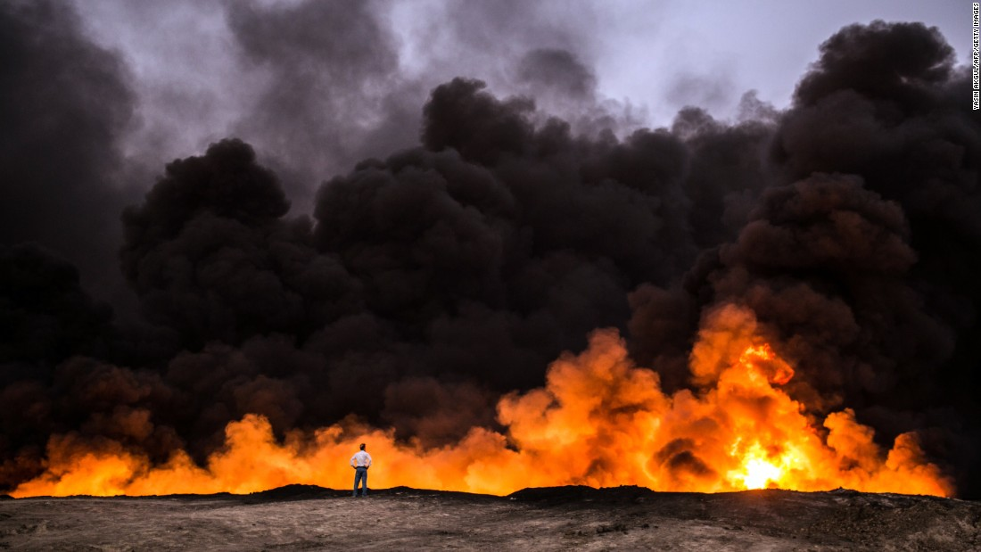 A man stands in front of a fire from oil that had earlier been set ablaze by members of ISIS in the Qayyara area on October 19.