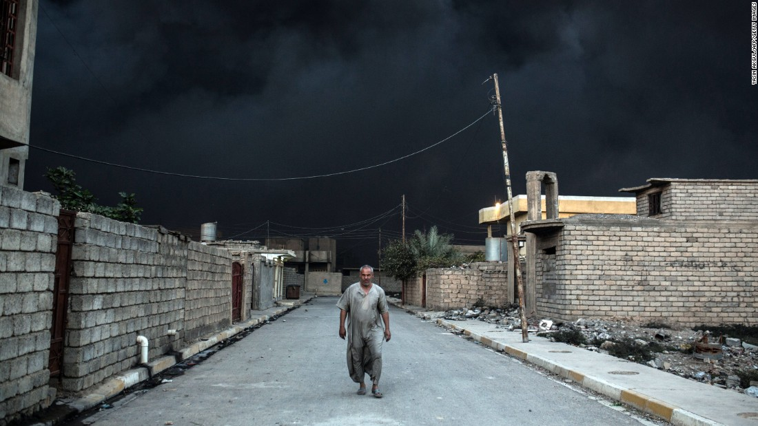 A street is covered with smoke from the Qayyara fire.