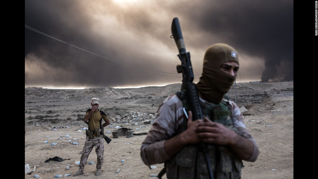 Iraqi soldiers look on as smoke rises from the Qayyara area.
