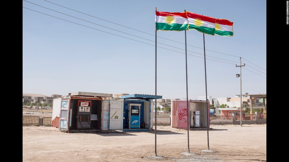 Kurdish flags fly in front of gas pumps on the side of the road. Grosso traveled between the cities of Kirkuk and Sulaymaniyah.