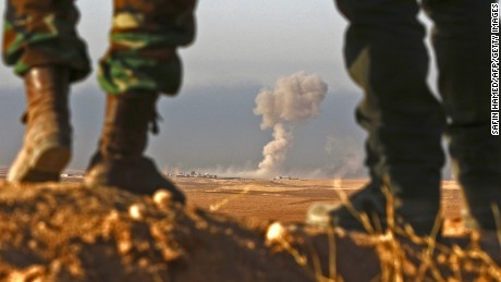TOPSHOT - Iraqi Kurdish Peshmerga fighters stand in an area near the town of Bashiqa, some 25 kilometres north east of Mosul, as smoke billows on October 20, 2016, during an operation against Islamic State (IS) group jihadists to retake the main hub city. Kurdish forces launched a fresh push against areas held by the Islamic State group around Mosul, pressing an offensive to retake the jihadists' last major stronghold in Iraq. / AFP / SAFIN HAMED        (Photo credit should read SAFIN HAMED/AFP/Getty Images)