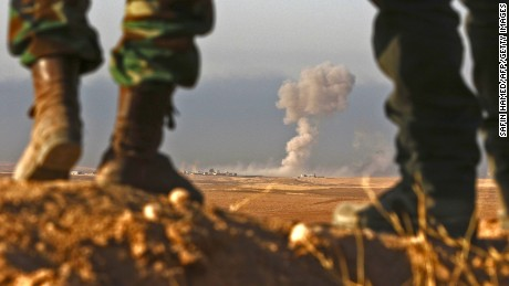 Iraqi Kurdish Peshmerga fighters stand in an area near the town of Bashiqa, some 25 kilometres north east of Mosul, as smoke billows on October 20, 2016, during an operation to retake the city from ISIS.