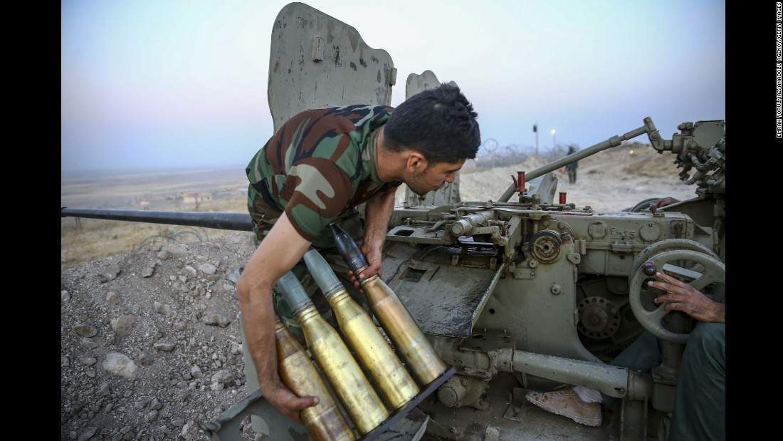 A member of the Peshmerga forces handles weaponry during an attack on ISIS targets near Naveran on October 20.