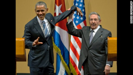 Cuban President Raul Castro, right,  tries to lift up the arm of President Barack Obama at the conclusion of their joint news conference at the Palace of the Revolution, Monday, March 21, 2016, in Havana, Cuba. (AP Photo/Ramon Espinosa)