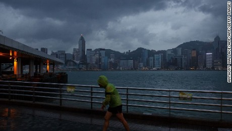 A man jogs along a promenade running along Victoria Harbour as Typhoon Haima approaches Hong Kong early on October 21, 2016, shortly after the typhoon signal eight warning was raised.