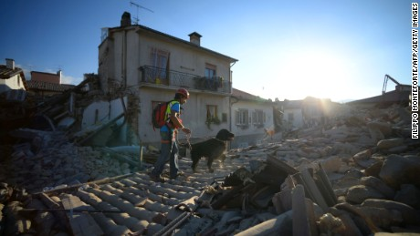 Rescue and emergency services personnel searches for victims with a dog in the central Italian village of Amatrice, on August 24, 2016 after a powerful earthquake rocked central Italy.