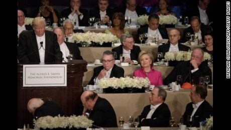 Democratic presidential nominee Hillary Clinton and others listen to Republican presidential nominee Donald Trump speak during the Alfred E. Smith Memorial Foundation Dinner at Waldorf Astoria October 20, 2016 in New York, New York. / AFP / Brendan Smialowski        (Photo credit should read BRENDAN SMIALOWSKI/AFP/Getty Images)