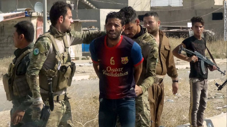 Kurdish security forces detain a suspected ISIS member on the outskirts of Kirkuk Saturday.