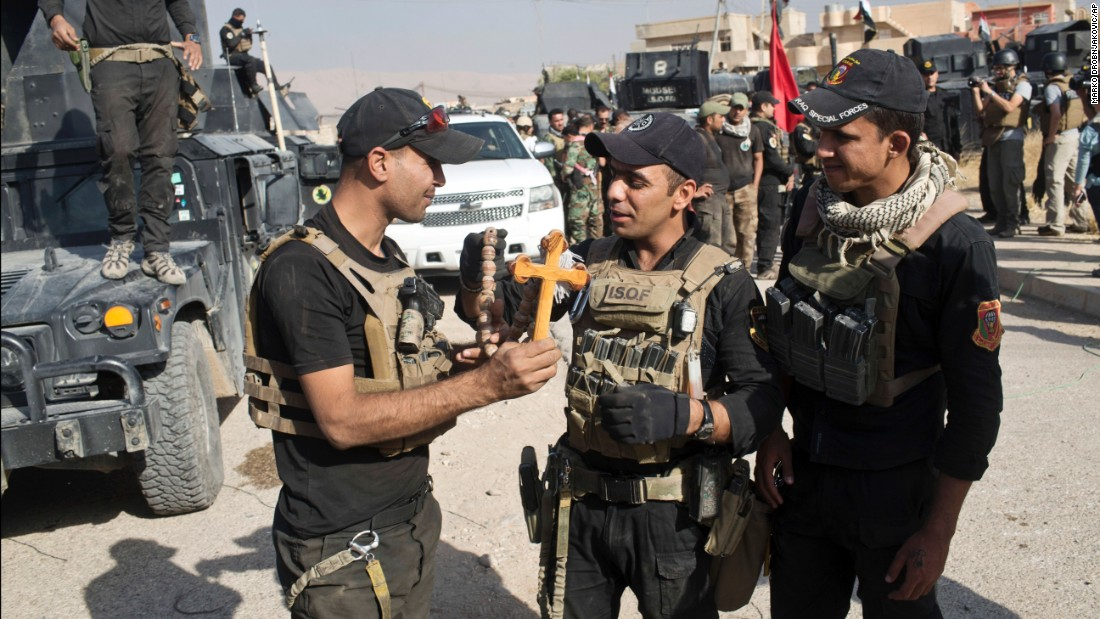 Iraqi special forces hold a cross found in the Christian town of Bartella on October 22. Iraqi forces recaptured Bartella but still faced some resistance in the area.