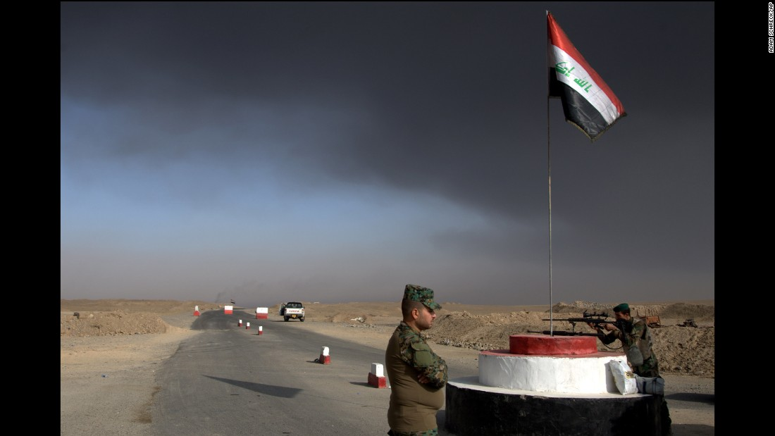 Iraqi troops guard a checkpoint October 22 near the village of Awsaja as smoke rises from fires that ISIS militants set at oil wells and a sulfur plant. The smoke and accompanying breathing problems have concerned US and coalition troops.