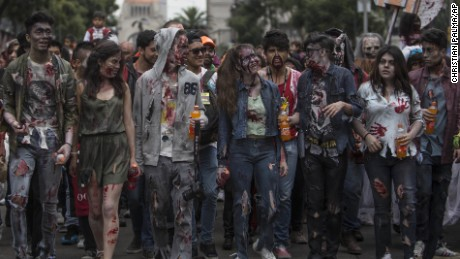 People dressed in rags and ghoulish makeup attend the annual Zombie Walk in Mexico City, Saturday, Oct. 22, 2016. (AP Photo/Christian Palma)