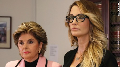 Jessica Drake stands with her attorney, Gloria Allred, as she holds a photo of Drake and Donald Trump during a news conference in Los Angeles on Saturday, Oct. 22, 2016.