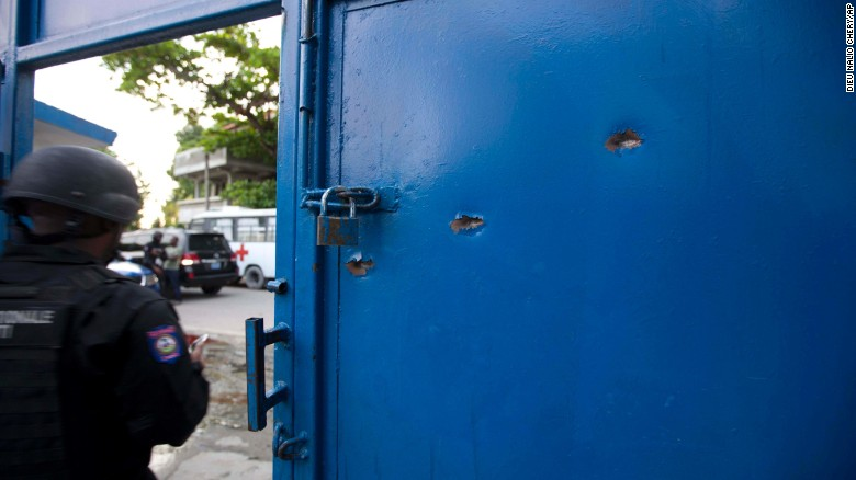 Bullet holes pierce the main gate of the Civil Prison after a jail break in the coastal town of Arcahaiea, Haiti.
