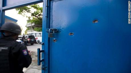 Bullet holes pierce the main gate of the Civil Prison after a jail break in the coastal town of Arcahaiea, Haiti.