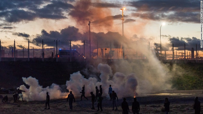 Smoke rises after French police fired tear gas into the Calais 'jungle' camp following refugees threw rocks towards the police vans in Calais, France on October 22.