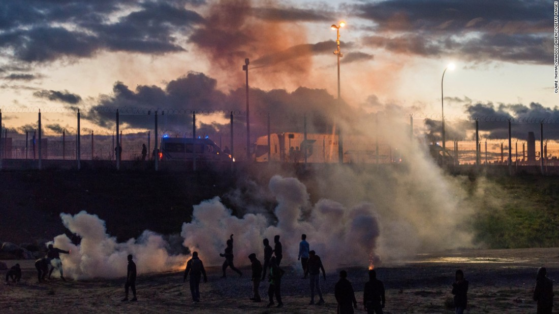 French police fire tear gas after refugees reportedly threw rocks at police vans near the camp on October 22.