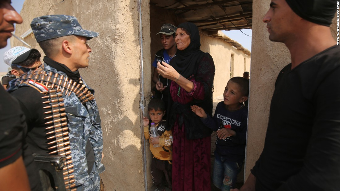 Iraqi forces talk with a family in al-Khuwayn on October 23.