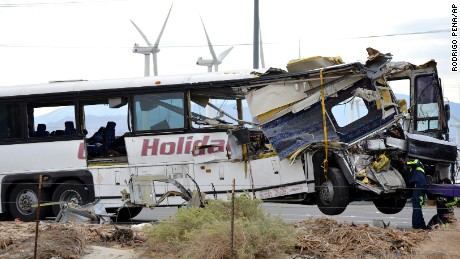 Workers prepare to haul away a tour bus that crashed with semi-truck on Interstate 10 just west of the Indian Canyon Drive off-ramp, in Desert Hot Springs, near Palm Springs, Calif., Sunday, Oct. 23, 2016. The tour bus and a semi-truck crashed on the highway in Southern California early Sunday, killing at least a dozen of people and injuring at least 30 others, some critically, the California Highway Patrol said. (AP Photo/Rodrigo Pena)