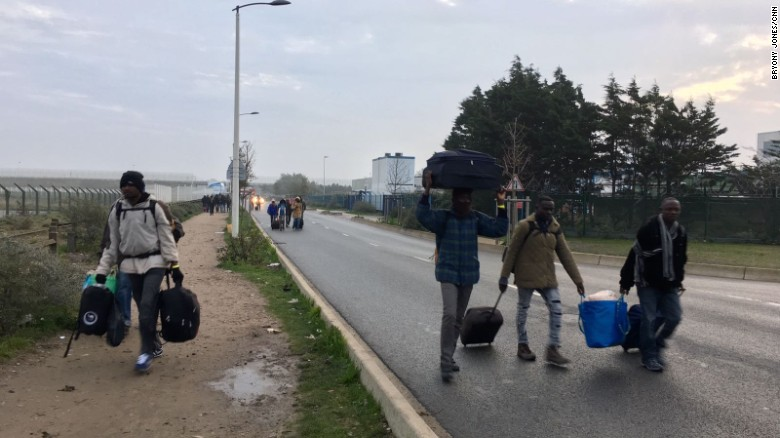 "Migrants from ""The Jungle"" in Calais make their way to a processing center, where the will either claim asylum in France or choose to return to their home countries."