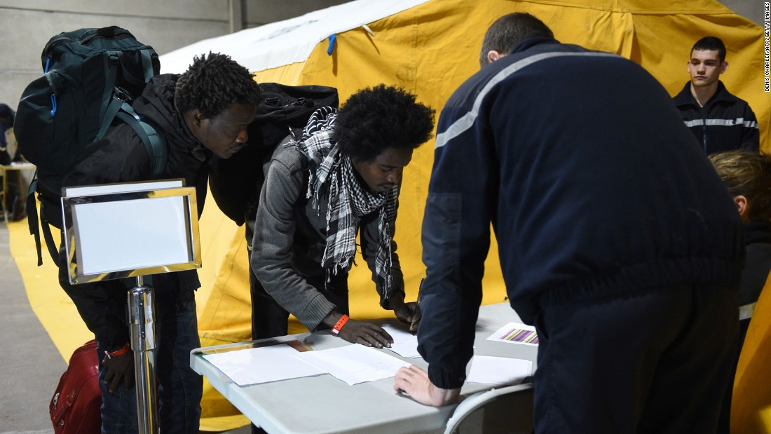Migrants register with French authorities before boarding buses that will transport them to shelters across France on October 24.