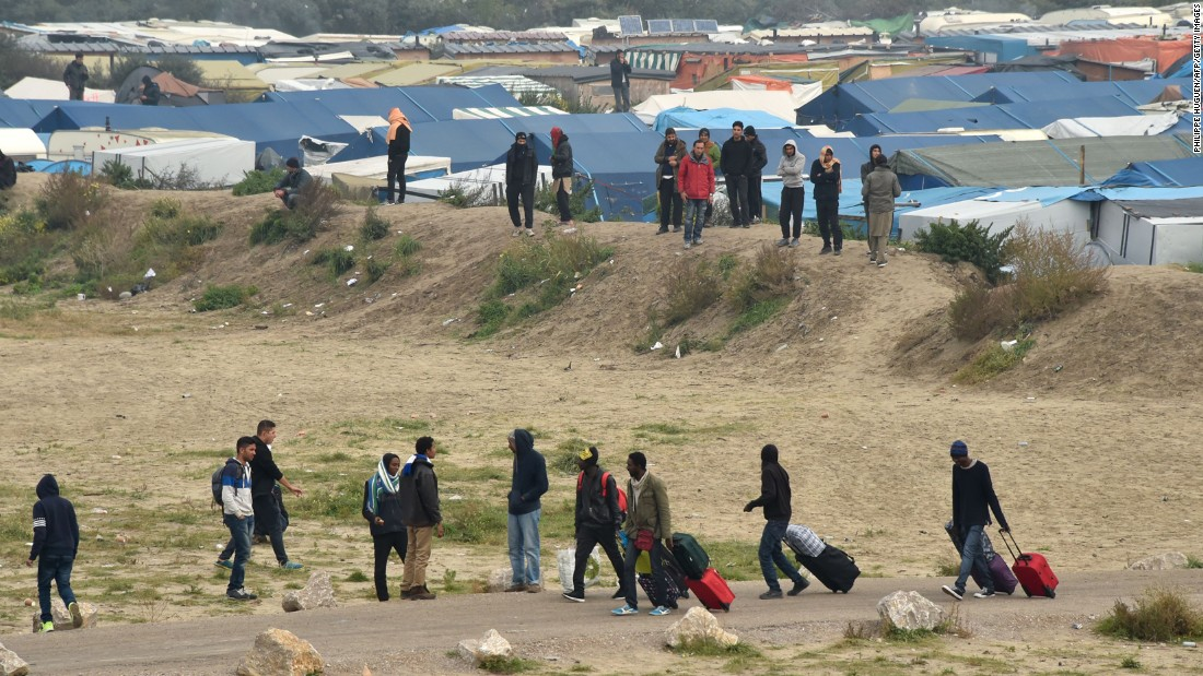 "Migrants leave their makeshift homes in the migrant camp known as ""The Jungle"" in Calais, France on Monday, October 24. People living in the camp have been told that the camp will be demolished in three days and that they can either apply for asylum in France or return to their home countries."