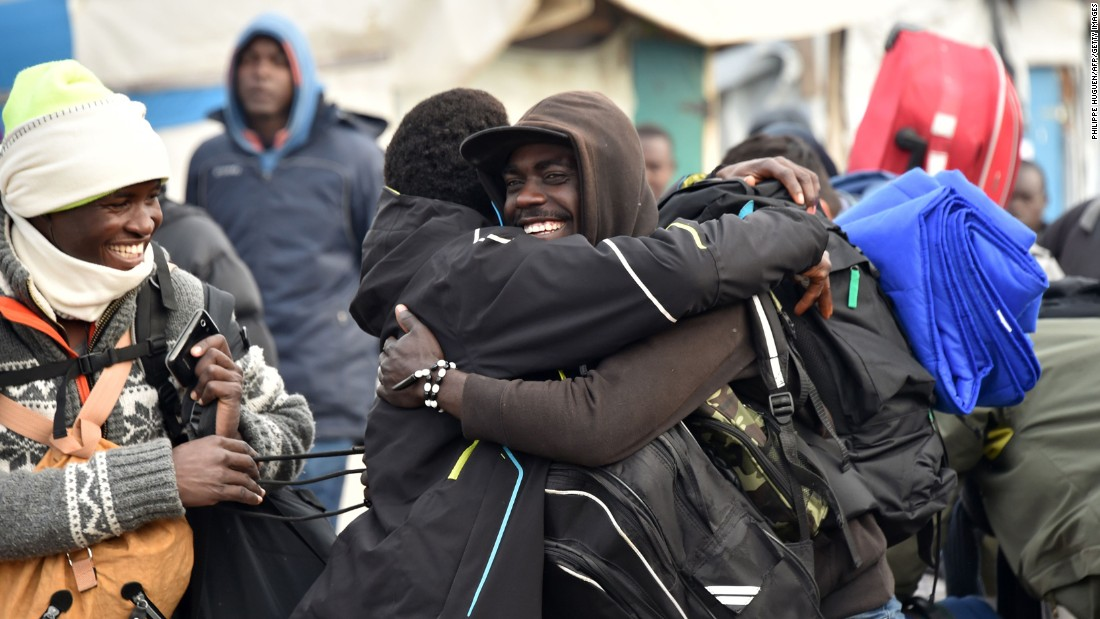 "Residents of the camp hug before departing the ""Jungle"" on October 24."