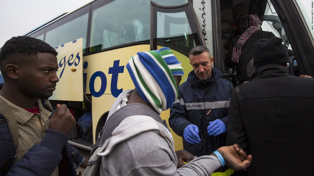 Migrants board buses that will transport them to shelters around France on October 24. Those applying for asylum will offered temporary accommodation in a shelter while their claim is processed.