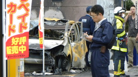Policemen and firefighters investigate a parking lot after an explosion in Utsunomiya, some 100 kilometres (60 miles) north of Tokyo, on October 23, 2016. One person was killed and at least two injured by two near-simultaneous blasts in a Japanese park on October 23, the local fire department said. / AFP / JIJI PRESS / JIJI PRESS / Japan OUT        (Photo credit should read JIJI PRESS/AFP/Getty Images)