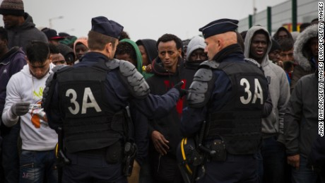 CALAIS, FRANCE - OCTOBER 24: Migrants queue behind a line of police at a reception point outside the Jungle migrant camp before boarding buses to refugee centres around France on October 24, 2016 in Calais, France. French authorities have begun to clear the estimated 7000 people from the Jungle migrant and refugee camp ahead of its demolition. (Photo by Jack Taylor/Getty Images)