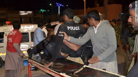 People transfer an injured police trainee to a hospital in Quetta , Pakistan, on October 24. At least four police trainees were injured and over 200 others held hostage by unknown militants who attacked a police training center.
