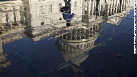 A pedestrian walks past the U.S. Capitol building as it is reflected in a puddle in Washington, D.C., U.S., on Friday, Aug. 26, 2016. House Speaker Paul Ryan said on a conference call today that the Military Construction, Veterans Affairs, and Related Agencies (MilCon-VA) spending bill and funding to combat the Zika virus will be priorities when the House returns after a recess on Sept. 6. Photographer: Andrew Harrer/Bloomberg via Getty Images