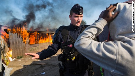 CALAIS, FRANCE - OCTOBER 25: A police officer stands guard after migrants burn down a shelter as authorities move in to clear the Jungle migrant camp on October 25, 2016 in Calais, France. Migrants are leaving the Jungle migrant and refugee camp by coach for a second day as French authorities clear the camp of an estimated 7000 people ahead of its demolition. (Photo by Jack Taylor/Getty Images)