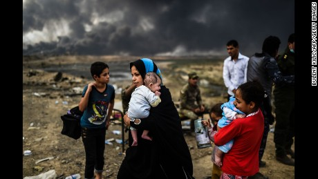 Iraqi families, who were displaced by the ongoing operation by Iraqi forces against jihadists of the Islamic State group to retake the city of Mosul, are seen gathering on an area near Qayyarah on October 24, 2016.